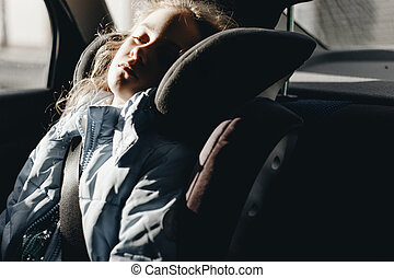 Seven-year charming girl sleeping in a children's car seat