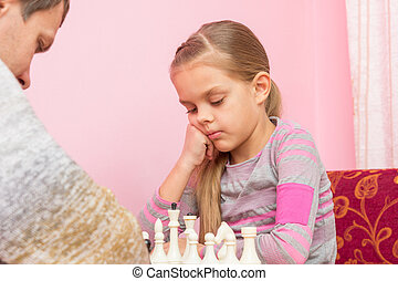 Seven-year daughter is thinking about the next move, playing chess