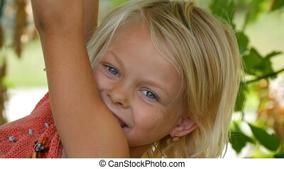 Seven-year funny dirty child girl blonde hangs on a tree branch outside the city on summer day close up view