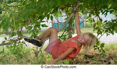 Seven-year funny dirty child girl blonde hangs on a tree branch outside the city on summer day