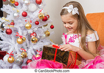 Seven-year girl in a beautiful dress is considering a gift sitting on the couch at Christmas tree