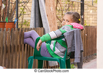 Seven-year girl is resting sitting on a chair in the yard and putting his feet on the wooden fence