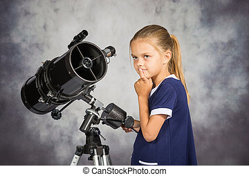 Seven-year girl looks at the sky while standing at the telescope