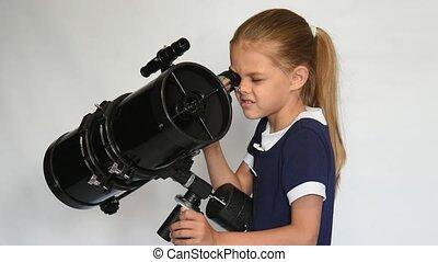 Seven-year girl looks in a reflector telescope