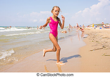 Seven-year girl runs on the beach from the sea