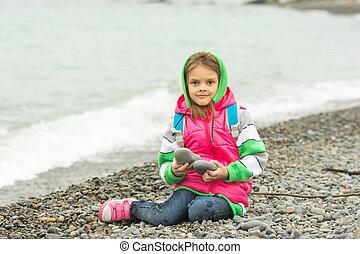 seven-year, menina, sentando, ligado, um, praia seixo, em, a, morno, roupas, e, olha, em, a, quadro