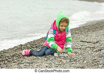 seven-year, menina, sentando, ligado, um, praia seixo, em, a, roupa morna, e, com, estusiasmo, jogos, com, pedras