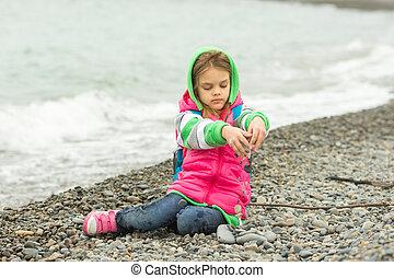 seven-year, menina, sentando, ligado, um, praia seixo, em, a, roupa morna, e, despeja, saída, através, dela, dedos, pequeno, pedras