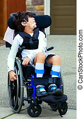Seven year old biracial disabled boy in wheelchair. Child...