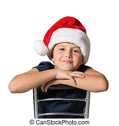 Seven year old boy in red hat cheerfully smiles