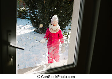 Seven-year-old cute girl in winter clothes is standing outside the door, on the street with snow in her hands and looking at the house smiling.
