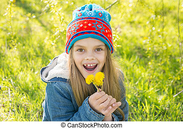 Seven-year-old girl in the spring is pleased with the blossoming dandelions