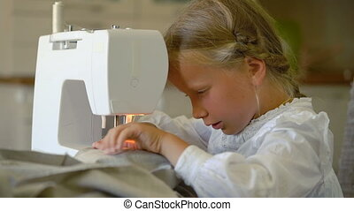 seven year old girl sews at home on a sewing machine,...