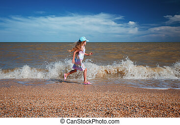 Seven years old girl in summer dress running along the sea at sunny day