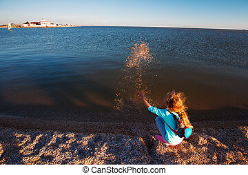 Seven years old girl on the beach at sunset time