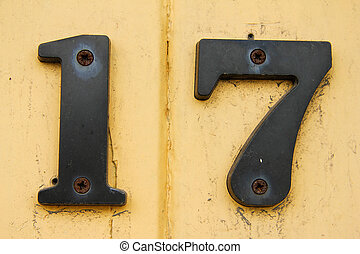 Weathered number 17 on painted yellow background