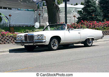 This is a picture of a white 1970's convertible on a street taken on a sunny day with the top down.