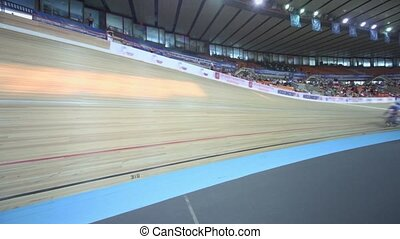 Several bicyclists ride track during race at stadium