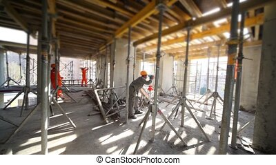 Several builder work in unfinished premises, one uses...
