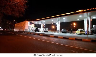 Several cars fill fuel at gas station in city at night