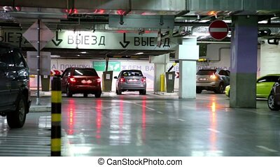 Several cars ride away from underground parking garage,...