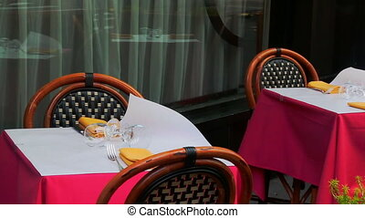 Several clients sit in restaurant, focus on glass with napkin and chopsticks at table