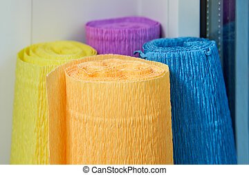 Several colored rolls of creped paper for crafts.