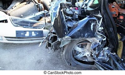 Several crashed cars stand on junkyard, closeup view in...