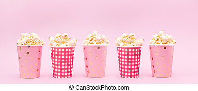 several cups of popcorn on a pink background