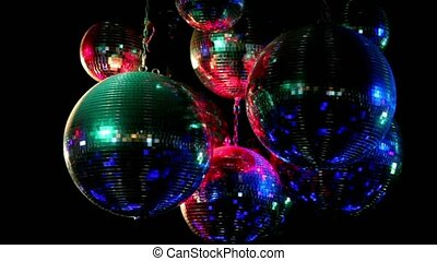 Several discoballs hang from ceiling and rotate, light is...