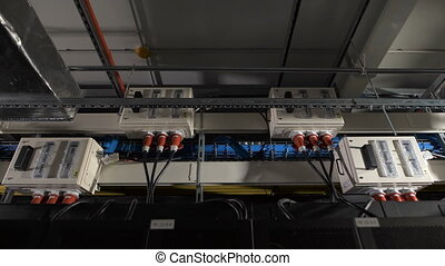 Several electric power units are equipped with a switch inside, attached under the ceiling in the industrial premises of IT companies. Devices connected to a common supply by cables with red plug.