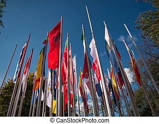 Several flagpoles with many flags in the wind
