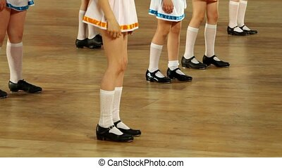 Several girls in shoes with taps and white skirts tap dance, only legs are visible
