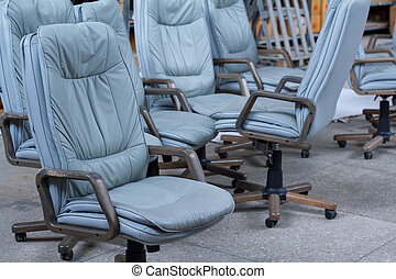 Several gray leather office chairs ready for packaging in a furniture warehouse, online furniture store