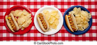 Several hotdogs on colored plates on a gingham background
