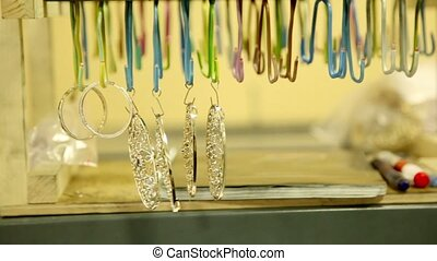 Several jewelry hang on hooks in a row, closeup view