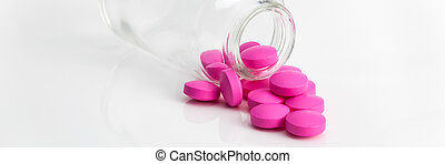 Several large bright pink tablets poured from a glass jar.