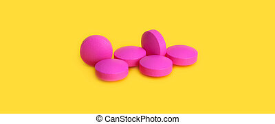 Several large pink tablets scattered on a yellow background. Side view.