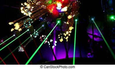 Several lasers emit green rays at background of shiny...