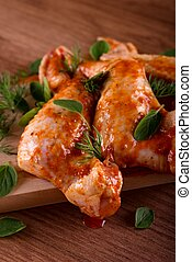 Several marinated chicken wings with green herbs
