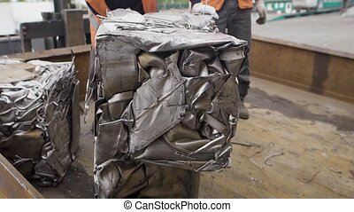 Pressed metal blocks, which were obtained after the processing of various parts, a man in a special uniform throws garbage squares, which appear underground in a common heap