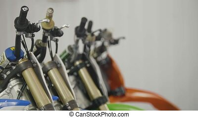 Several motorcycle in the garage - handlebars of enduro...