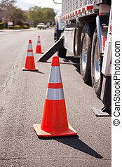 Several Orange Hazard Cones and Utility Truck in Street.