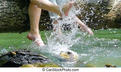 Several people play with their feet in the water on a fallen tree.