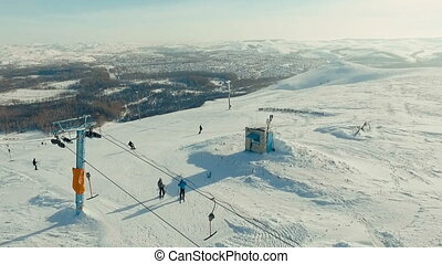 Several people ride away from the ski-lift.