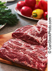 Several pieces of beef meat are lying on a board.