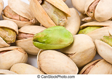 Several pistachio nuts naked and in shell close up