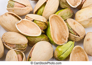 Several pistachio nuts naked, empty shells  and in shell close up