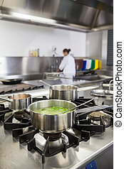 Several pots cooking on hotplate in professional kitchen