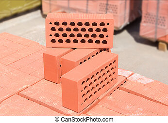 Several red perforated bricks against of pallets of bricks closeup